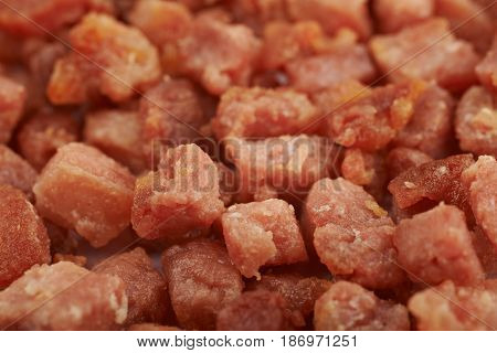 Surface covered with the fried cube bacon bits as a food backdrop composition with a shallow depth of field