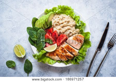 Balanced nutrition. Fresh salad from quinoa chicken breast avocado spinach lettuce and tomatoes. Healthy food. Portion plate. Top view