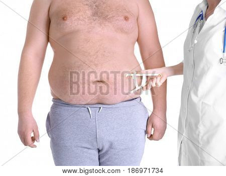 Female doctor measuring fat on man's belly using caliper, on white background. Weight loss concept