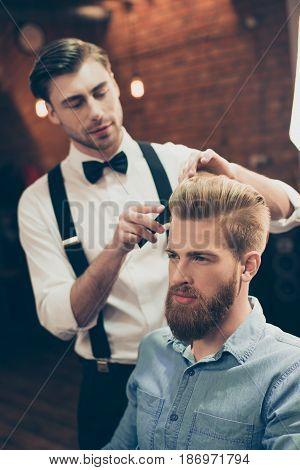 Barber Shop Classy Dressed Handsome Stylist Is Doing A Perfect Hairstyle To A Bearded Guy In Caual J