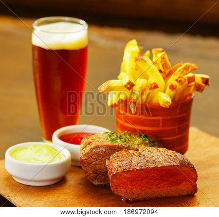 Close up of a well-done grilled marinated beef flank steak with ketchup, mustard and french fries with a glass of beer on wooden board.