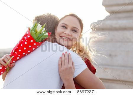 Happy woman with bouquet embraced by boyfriend outdoor