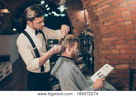 Red Bearded Guy Is Reading A Magazine In A Barber Shop While Getting Bren New Haircut From A Classy