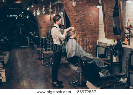 Barber shop classy dressed specialist is styling the hair of a client. Salon is retro and vintage. Customer is a young bearded man covered with cape poster