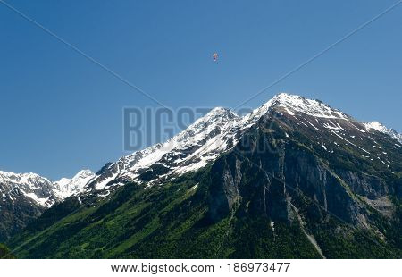 Paragliding In The Swiss Alps Above Snow Covered Peaks