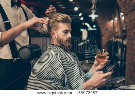 Chill Out At The Barber Shop. Side View Of Handsome Young Red Bearded Man Drinking Scotch And Browsi