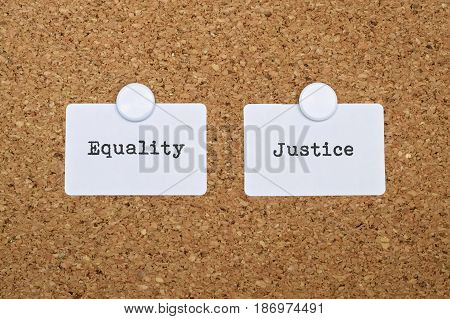 Words Equality and Justice written on two white stickers pinned on cork board