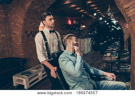 Young Blond Stylish Guy In A Casual Jeans Outfit Is Showing To Barber Shop Worker How He Wants His B