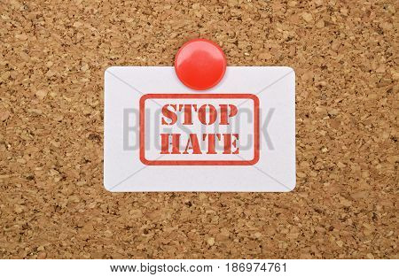 Text Stop Hate written on a white sticker pinned on cork board