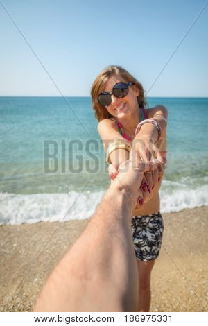 Girl holding hand of her boyfriend on the beach. Focus is on the hands.