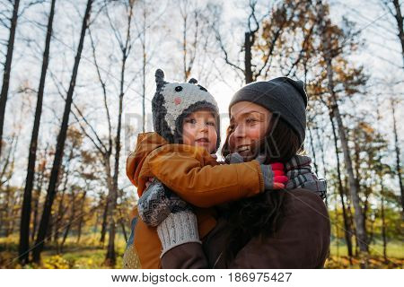 mother gently holding daughter in her arms touching noses in the park