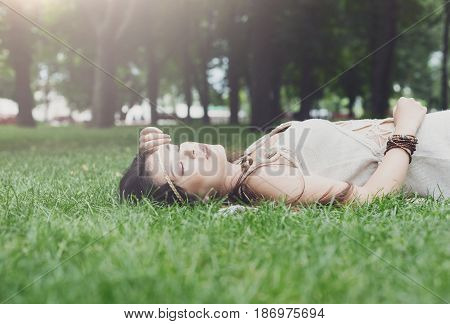 Beautiful asian girl lying on grass in summer park, happy and smiling. Female korean teenager relax outdoors at sunny day. Attractive pretty woman dreaming, looking up