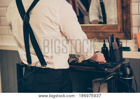 Back View Of A Barber Shop Stylist Organizing His Tools And Equipment,  He Is Wearing White Shirt An