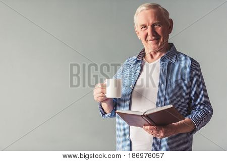 Handsome old man in casual wear is holding a book and a cup looking at camera and smiling on gray background