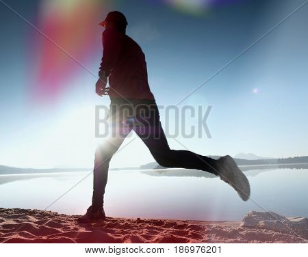 Running man on beach. Sportsman run in baseball cap jogging guy during the sunrise above sandy beach. Man jumping on the beach at sunset