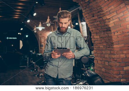 Casual men`s life. Perfect! Harsh stylish red bearded man in a barber shop is browsing on his tablet serious and concentrated waiting to get a haircut poster