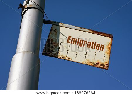Word Emigration written on a white metal board