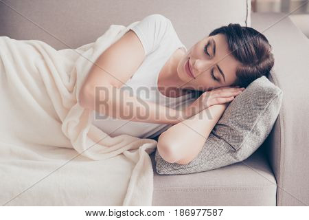 Close Up Of A Young Gorgeous Brunette Sleeping On The Beige Cozy Sofa. Her Head Is On Grey Pillow An