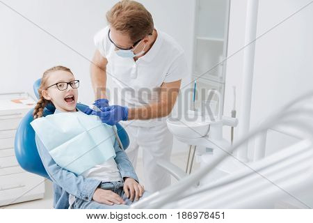 Following orders. Yung bright positive girl having her teeth cured while the doctor using special equipment for conducting a procedure