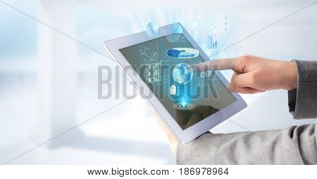 Digital composite of Hands touching tablet and blue graphics and flares and white background
