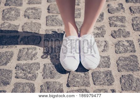 Cropped Close Up Photo Shot Of A Girl`s Legs In White Gumshoes On The Cobbles. She Is On Vacation, H