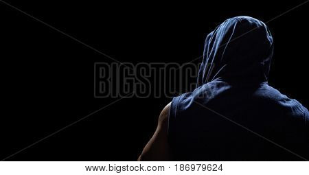 Digital composite of Back of man in hoodie against black background