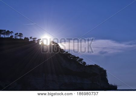 Sunrays with cliff, trees and trabocco fishing system