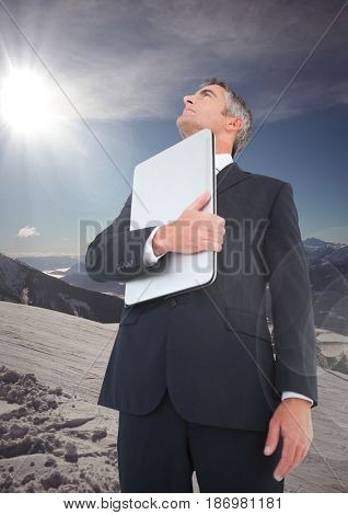 Digital composite of Business man with laptop looking up on mountain