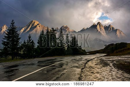 Travel destination concept image. Composite landscape of High Tatra mountain ridge. Curve asphalt road through spruce forest. Peaks lit by the sun in stormy weather with dramatic sky.