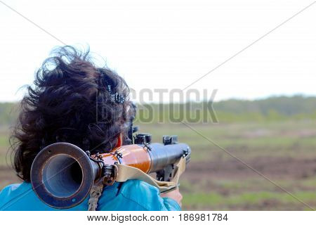 A woman is aiming from a hand grenade launcher.