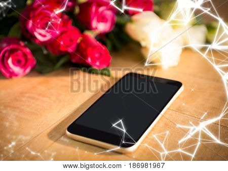 Digital composite of Phone on table with roses and white network overlay
