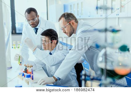 Professional Scientists In White Coats Working Together In Chemical Laboratory