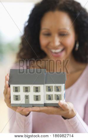 Hispanic woman holding miniature house