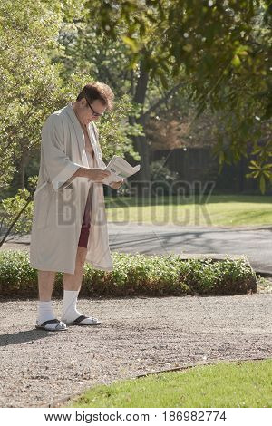 Man holding newspaper in driveway