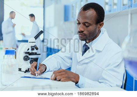 African american scientist in white coat taking notes while working in laboratory laboratory researcher concept