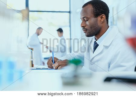 African American Scientist In White Coat Taking Notes While Working In Laboratory, Laboratory Resear