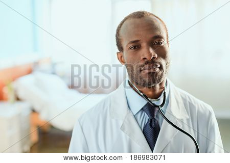 Portrait Of Serious Doctor With Stethoscope Standing In Hospital Chamber