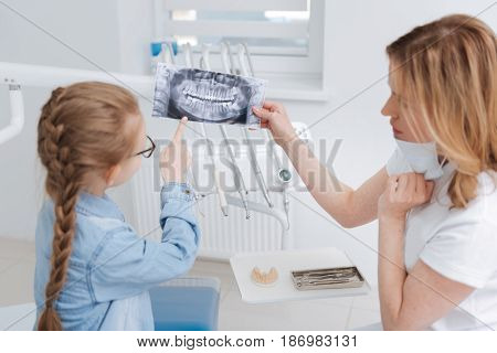 What does this mean. Dedicated competent young doctor looking at the scan of girls jaw and young lady being curious and asking questions about treatment