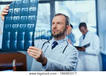Portrait Of Focused Doctor Analyzing X-ray Picture With Colleagues Behind