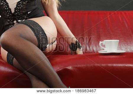 Erotic fashion concept. Sexy lady wearing alluring black sensual lingerie sitting on the couch having cup of coffee or tea