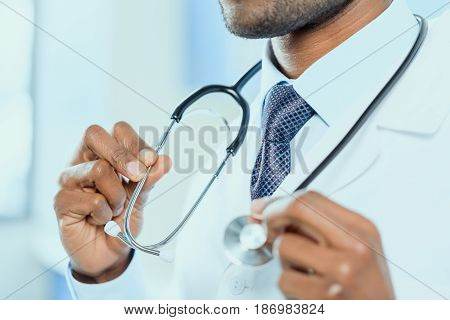 Partial Side View Of Doctor Holding Stethoscope In Hands