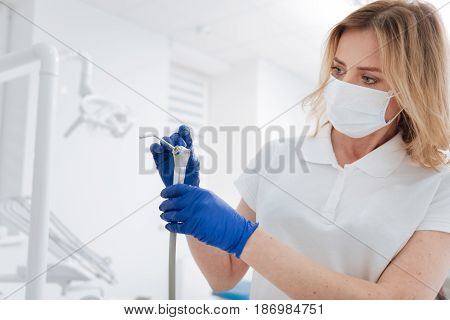 Perfect device. Considerate competent trained dentist maintaining and cleaning professional equipment she employing while treating her patients
