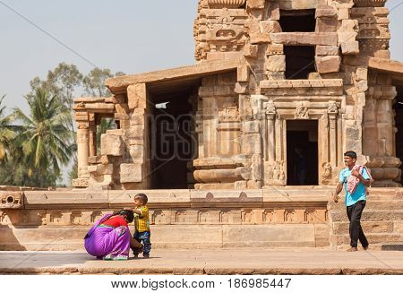PATTADAKAL, INDIA - FEB 9, 2017: Happy asian family having fun near ancient Hindu temple on February 9, 2017. UNESCO World Heritage site with stone carved structures of 7th and 8th-century
