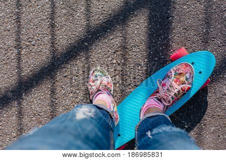 Close up of feet of a girl in pink sneakers rides on blue penny skate board with pink wheels. Urban scene, city life. Sport, fitness lifestyle.