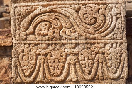 Patterned design of stone relief on wall of 7th century temple in Pattadakal of Karnataka, India. UNESCO World Heritage site with stone carved temples.