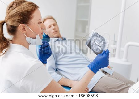 It will take some effort. Distinguished clever focused doctor examining patients jaw scan and analyzing the results while developing a plan of his treatment