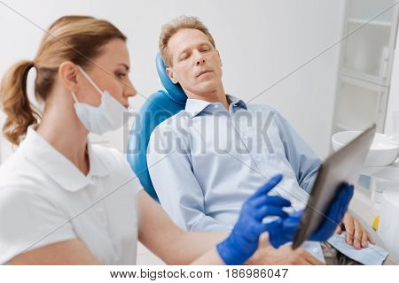 I will make it clear for you. Competent attentive delicate dentist making sure the patient understanding everything while illustrating his diagnosis with the data on her gadget