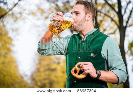 Bavarian man in traditional Tracht drinking beer out of a huge mug, holding pretzel in other hand