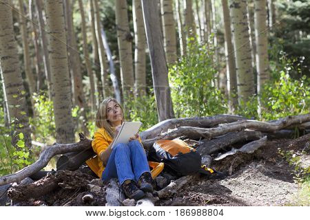 Hispanic woman writing in journal in forest