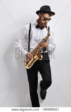 Jazz musician leaning against a white wall and playing saxophone